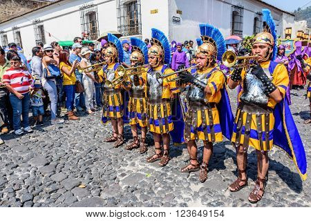Antigua Guatemala - March 24 2016: Locals dressed as Romans signal approach of Holy Thursday procession in colonial town with most famous Holy Week celebrations in Latin America.