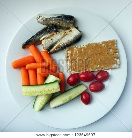Picture of a white plate containing sardines,carrots,cucumber,tomatoes and crackers.