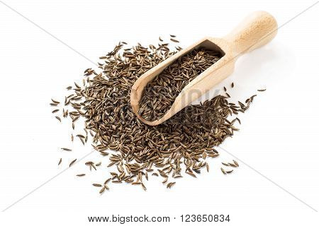 Dry cumin seeds in a wooden scoop on a white background
