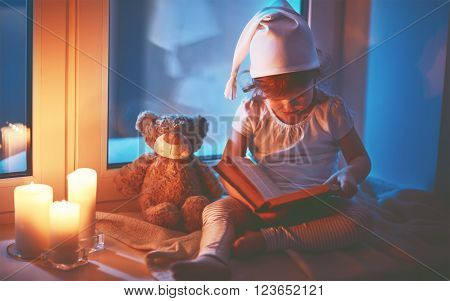 little child girl reading a book by window before bedtime