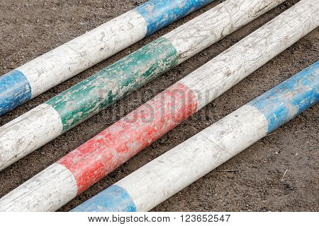 Colorful bars from horse jumping obstacles laying on the ground