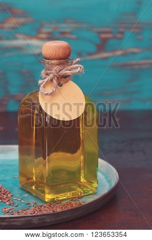 Linseed oil or flaxseed oil in a bottle,  empty tag. Macro, selective focus, vintage toned image