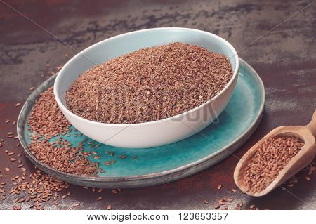 Flax seeds in bowl. Whole and ground flax seed  in ceramic dishes and wooden spoon.  Macro, selective focus, vintage toned image