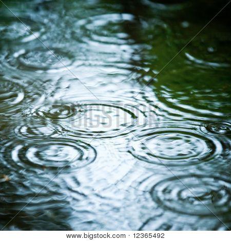 La lluvia cae en un charco de ondulación