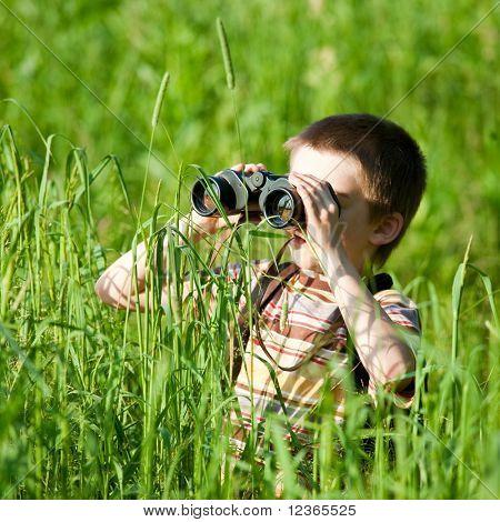Kleiner Junge in einem Feld Blick durchs Fernglas