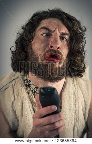 Silly grunting cave man confused by television remote
