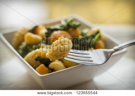 Vegetarian gnocchi dish with squash kale and mushrooms