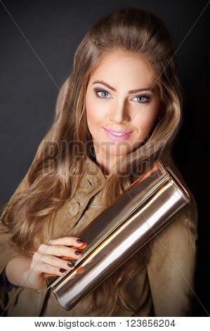 Beautiful classy woman holding an elegant golden bag