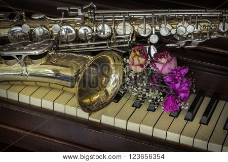 Old and worn Jazz saxophone and piano with dried roses