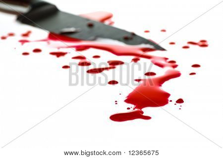 Red blood splatter with  kitchen knife in background, shallow DOF