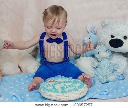Baby boy crying while eating his birthday party cake. Smash the cake party. Portrait of cute toddler crying while playing smash cake.