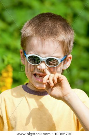 Portrait of a young boy wearing sunglasses picking his nose