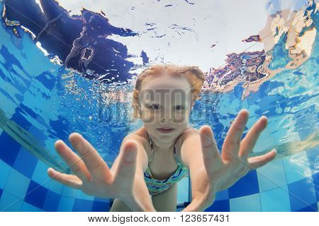 Funny face portrait of little baby girl swimming and diving underwater with fun in pool. Active healthy lifestyle water sport activity and lessons with parents on summer family vacation with child.
