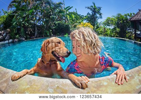 Funny portrait of smiley woman playing with fun and training golden retriever puppy in outdoor swimming pool. Popular dog like companion outdoor activity and game with family pet on summer holiday.