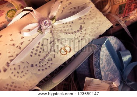 Vintage wedding invitation envelope with ribbon among git boxes