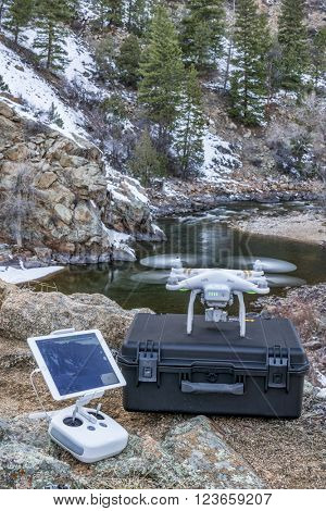 Big Narrows, Poudre Canyon, CO, USA - March 12, 2016:  DJI Phantom 3 quadcopter drone is  ready to take off in a mountain river canyon