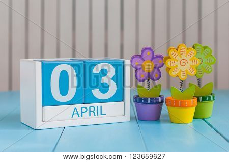April 3rd. Image of april 3 wooden color calendar on white background with flowers. Spring day, empty space for text.