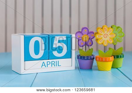 April 5th. Image of april 5 wooden color calendar on white background with flower. Spring day, empty space for text.