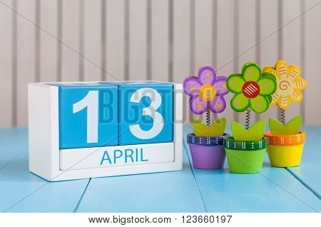 April 13th. Image of april 13 wooden color calendar on white background with flowers. Spring day, empty space for text. World Rock-n-roll Day.