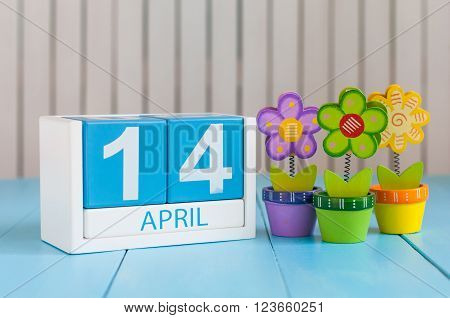 April 14th. Image of april 14 wooden color calendar on white background with flowers. Spring day, empty space for text.