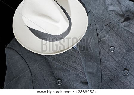 fedora hat and double-breasted formal pinstripe grey suit jacket on black