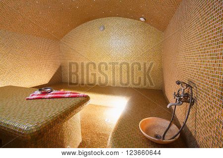 Interior of Turkish sauna, classic Turkish hammam at spa center. Spa, relaxation and resort health care center interior. Decorated in golden colors. Eastern hammam.