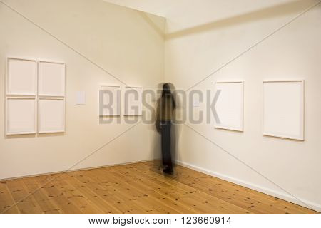 Woman in blurred motion studying picture in exhibition