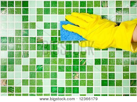 Hand in yellow protective glove  cleaning mosaic wall