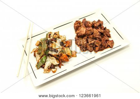 The Chinese fried beef in sweet-sour sauce and stewed vegetables. On a white background
