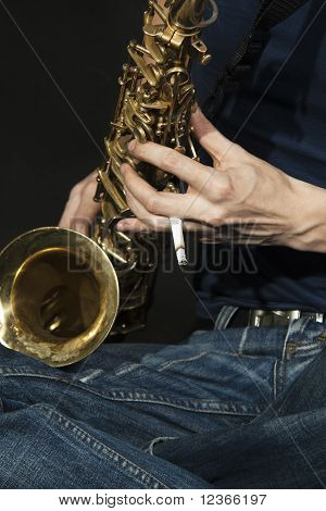 close up cross legged junge Jazzman spielt ein Saxophon