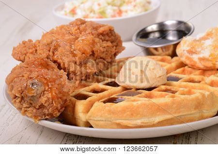 Delicious chicken and waffles with maple butter, honey and maple syrup.
