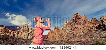 Trail runner woman drinking water and running in mountains inspirational landscape. Training and working out jogging and exercising outdoors in nature. Panoramic view on rocky footpath on Tenerife Canary Islands Spain