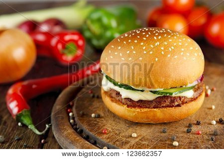 Classic american burger food. Hamburger at wood. Wooden desk with hamburger and fresh vegetables composition. Burger with cheese, beef, cucumber, lettuce. Cheeseburger at wooden background.