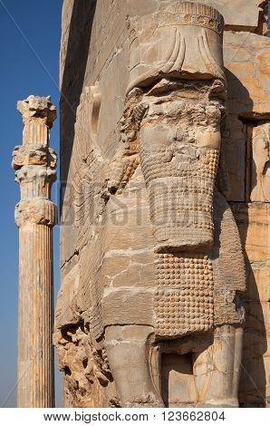 Persian Lamassu and a column with typical Achaemenid architecture in the ruins of ancient city of Persepolis in Shiraz.