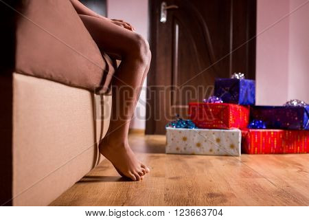 Barefooted child sitting beside presents. Presents near afro kid's bed. Wake up - it's Christmas. Get up and start celebrating.