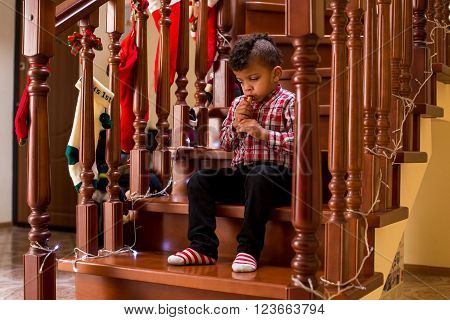 Mulatto child plays wind instrument. Boy playing flute during Christmas. Take your time, maestro. So young yet so skillful.