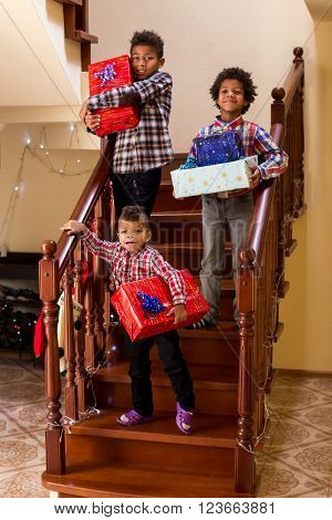 Boys with presents on stairs. Three children holding Christmas presents. Children's favorite holiday. That sweet joy of holiday. ** Note: Soft Focus at 100%, best at smaller sizes