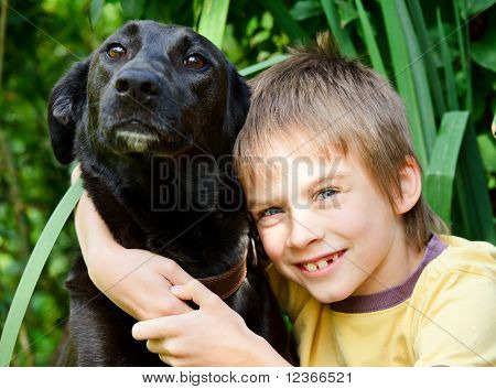 Young boy hugging  black dog outdoors