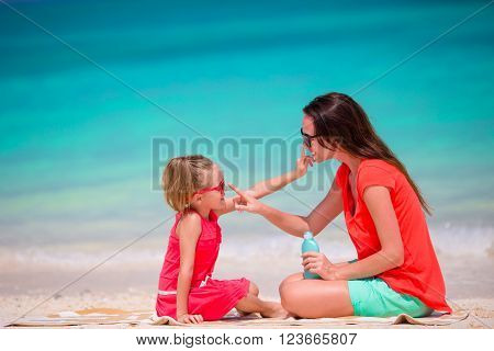 Young mother applying sun cream on her kid