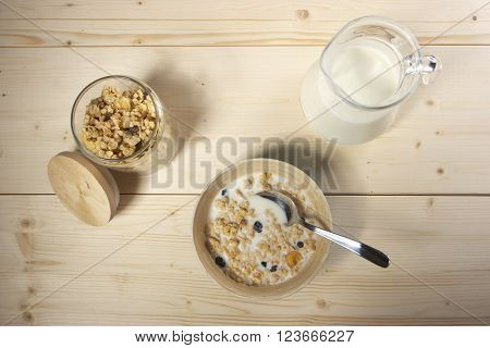 Delicious and healthy cereal in bowl with milk on table