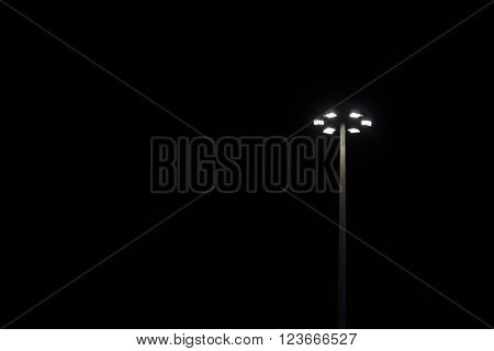 a bright lamppost in the pitch-black night