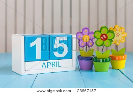 April 15th. Tax Day. Image of april 15 wooden color calendar on white background with flowers. Spring day, empty space for text.