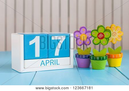 April 17th. Image of april 17 wooden color calendar on white background with flowers. Spring day, empty space for text. Tax Deadline.