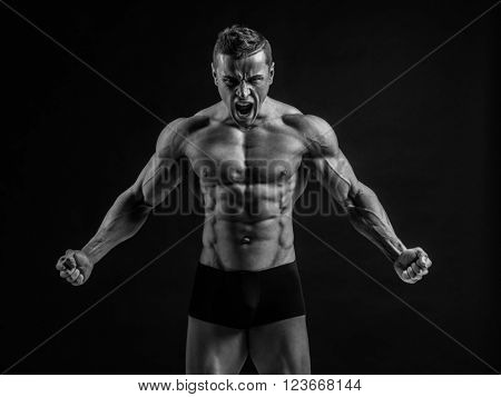 Young muscular bodybuilder posing over black background.