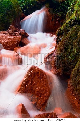 Cascades In Rapid Stream Of Mineral Water. Red Ferric Sediments On Big Boulders