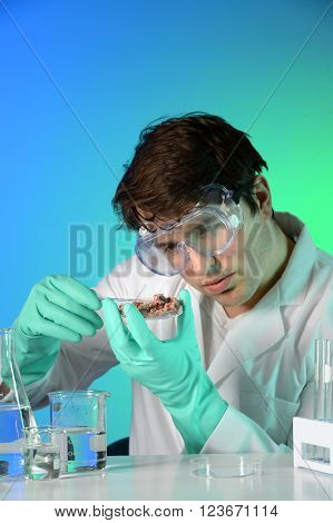 Young scientist testing meat on Petri dish in laboratory