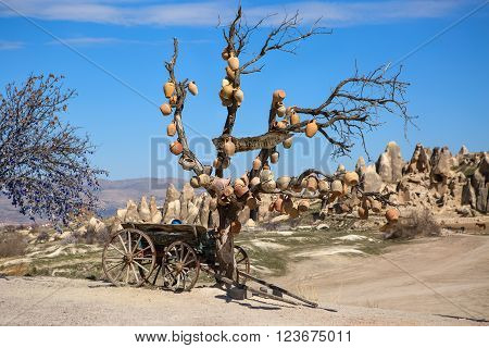 Lot of painted clay pots are hanging on the naked tree. There is a old cart under the tree. On the left there is a tree with hanging decoratiions. On the background there is rock formation and the blue sky with several clouds.
