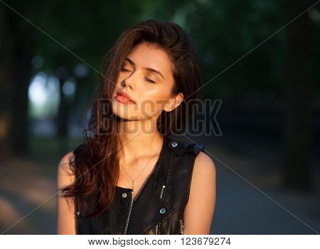 Closeup portrait of dreamy young beautiful brunette woman in black leather jacket posing with closed eyes on sunset outdoors  with blurry foliage background