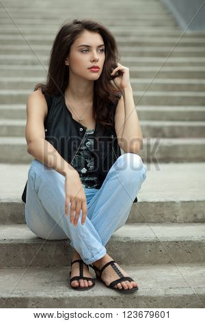 Young thoughtful fashionable brunette woman in black leather jacket posing sitting on concrete stairway