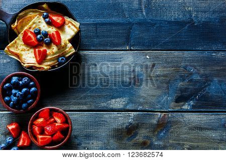 Top view of crepes with fresh berries on rustic wooden background with space for text. Pancake.